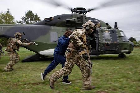 Kommandosoldaten des Kommando Spezialkräfte (KSK) der Bundeswehr demonstrieren bei einem Videodreh den Abtransport einer befreiten Geisel mittels eines Helikopters. Foto: Marijan Murat/dpa