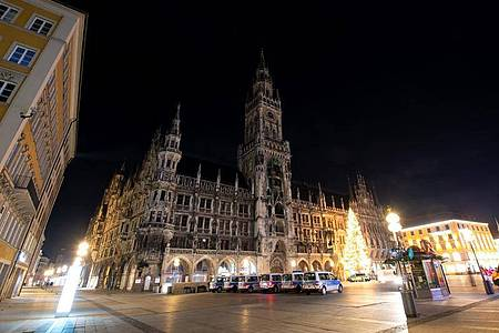 Polizisten und Sicherheitsmitarbeiter der MVG stehen auf dem ansonsten menschenleeren Marienplatz im Zentrum von München. Auch an Silvester gilt in Bayern die nächtliche Ausgangsbeschränkung ab 21 Uhr. Foto: Sven Hoppe/dpa