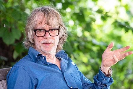 Musiker Helge Schneider spricht in seinem Garten mit einem Journalisten. (Archivbild). Foto: Caroline Seidel/dpa