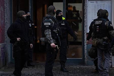 Polizisten und SEK-Beamte stehen vor einem Haus an der Stresemannstraße in Kreuzberg. Am frühen Morgen des zweiten Weihnachtstages fielen hier Schüsse. Vier Männer wurden schwer verletzt. Foto: Paul Zinken/dpa