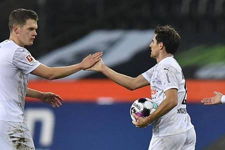 Mönchengladbachs Matchwinner Jonas Hofmann (r) und sein Mitspieler Matthias Ginter jubeln. Foto: Martin Meissner/AP/Pool/dpa