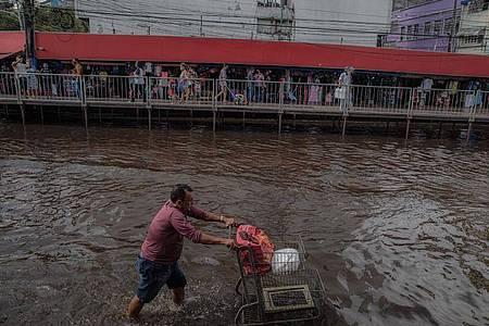 Ein Mann schiebt einen Einkaufswagen durch eine überschwemmte Straße. Die Flüsse rund um die brasilianische Amazonas-Metropole Manaus haben nach starkem Regen Rekordstände erreicht und heftige Überschwemmungen verursacht. Foto: Lucas Silva/dpa