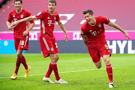 FCBayerns Doppel-Torschütze Robert Lewandowski (r), Leon Goretzka (l) und Thomas Müller jubeln über den Treffer zum 2:0. Foto: Matthias Balk/dpa