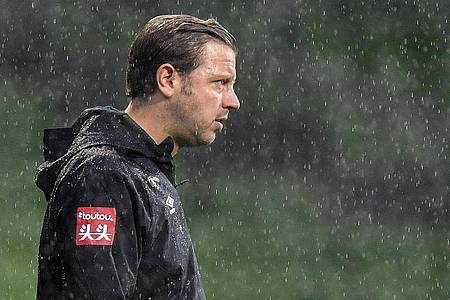 Bremens Cheftrainer Florian Kohfeldt steht im Regen. Foto: Martin Meissner/AP POOL/dpa