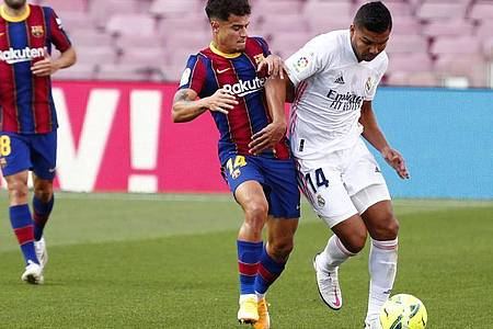 Real Madrids Casemiro (r) und FC Barcelonas Philippe Coutinho (l) beim Kampf um den Ball mit. Foto: Joan Monfort/AP/dpa