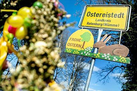 """Ein Schild mit der Aufschrift """"Frohe Ostern"""" hängt unter dem Ortsschild am Ortseingang von Ostereistedt. Foto: Hauke-Christian Dittrich/dpa"""