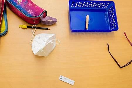 Ein Schnelltest, eine FFP2-Maske sowie andere Utensilien liegen bei einem Probelauf mit Corona-Schnelltests an der Grundschule in der Köllnischen Heide in Berlin-Neukölln auf einem Schultisch. Foto: Christoph Soeder/dpa