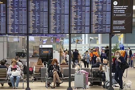 Passagiere sitzen auf dem internationalen Flughafen Scheremetjewo in Moskau unter einer Fluginformationstafel. Russland nimmt trotz der Corona-Pandemie den regulären Flugverkehr mit acht Ländern wieder auf. Foto: Alexander Zemlianichenko Jr/XinHua/dpa
