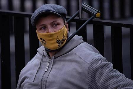 Ein Umweltaktivist von Extinction Rebellion (XR) hat sich mit einem Bügelschloss an einem Gitter am Bundesverkehrsministerium angeschlossen. Foto: Paul Zinken/dpa
