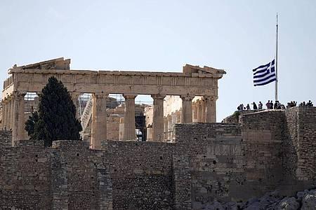 Die griechische Flagge weht nach dem Tod des griechischen Komponisten Mikis Theodorakis vor dem Parthenon-Tempel auf Halbmast. Foto: Thanassis Stavrakis/AP/dpa