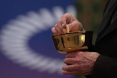 Ein Mitglied der Kirchengemeinde hält während eines Gottesdienstes mit Abendmahl im katholischen Dom St. Bartholomäus vor dem Logo des ÖKT eine Oblate in der Hand. Foto: Sebastian Gollnow/dpa