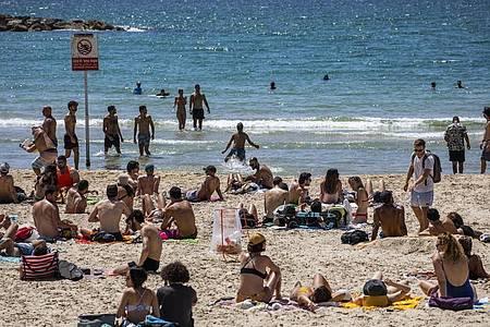 Menschen verbringen den Tag in der Sonne am Strand in Tel Aviv. Foto: Ilia Yefimovich/dpa