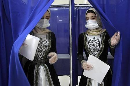Frauen in tschetschenischer Nationaltracht verlassen eine Wahlkabine in Grosny. Bei der von Manipulationsvorwürfen überschatteten Wahl der neuen Staatsduma hat sich die Kremlpartei Geeintes Russland laut ersten Ergebnissen als stärkste Kraft behauptet. Foto: Musa Sadulayev/AP/dpa