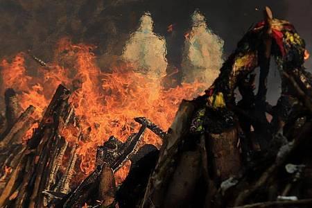 Szenen einer Masseneinäscherung von Opfern, die an den Folgen einer Corona-Infektion gestorben sind, auf dem Gelände eines Krematoriums in Neu Delhi. Foto: Naveen Sharma/SOPA/ZUMA Wire/dpa