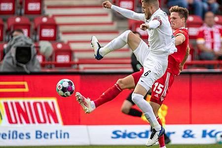 Jeffrey Gouweleeuw (l) vom FC Augsburg kämpft gegen Union-Spieler Marius Bülter um den Ball. Foto: Andreas Gora/dpa