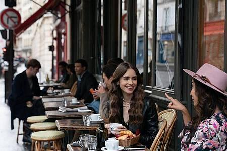 Emily (Lily Collins, m) sitzt mit einer Freundin im Café - Filmszene aus der ersten Staffel der Netflix-Serie «Emily in Paris». Foto: Stephanie Branchu/Netflix © 2020/dpa