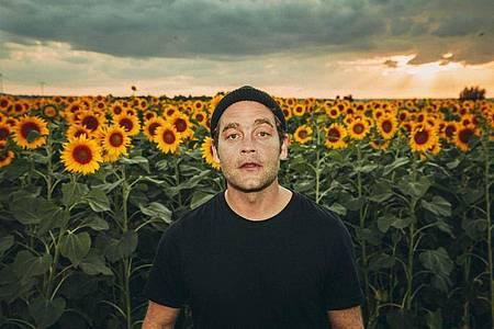 Der Sänger Bosse zeigt sich in einem Sonnenblumenfeld. Foto: Marco Sensche/Universal Music/dpa