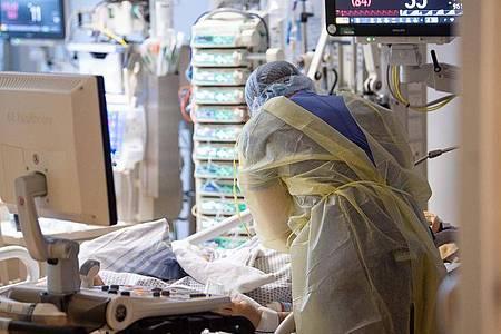 Ein Intensivpfleger arbeitet auf einer Intensivstation an einem Covid-19-Patient. Foto: Sebastian Gollnow/dpa