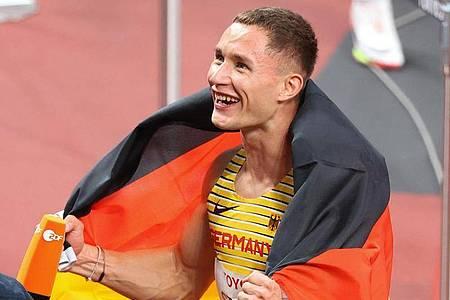 Goldmedaillengewinner Felix Streng jubelt nach dem Rennen mit der deutschen Fahne. Foto: Karl-Josef Hildenbrand/dpa