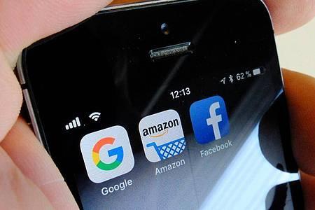 Logos der US-Internetkonzerne Google (l-r), Amazon und Facebook sind auf dem Display eines iPhons. Foto: Stefan Jaitner/dpa