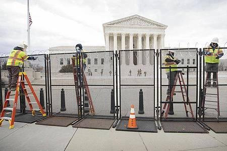 Arbeiter stehen am Sicherheitszaun vor dem US-Kapitol (Archivfoto vom 22. Januar). Foto: Mark Finkenstaedt/ZUMA Wire/dpa
