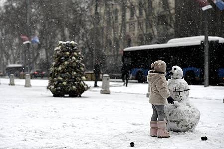 Ein Mädchen baut auf einer Straße in Madrid einen Schneemann. Foto: Óscar Cañas/EUROPA PRESS/dpa