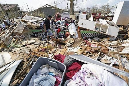 Jose Duran (l) hilft seiner Mutter Cruz Palma, die Überreste ihres Hauses nach dem Hurrikan Ida zu durchsuchen. Foto: David J. Phillip/AP/dpa