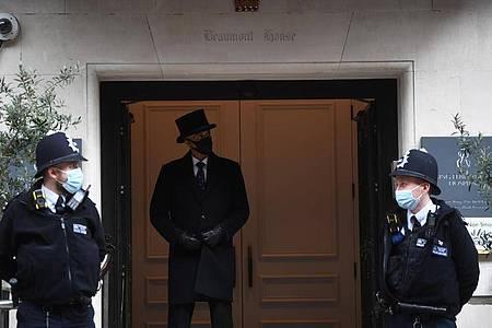 Ein Pförtner und zwei Polizisten bewachen den Haupteingang des King Edward VII. Krankenhauses. Foto: Victoria Jones/PA Wire/dpa