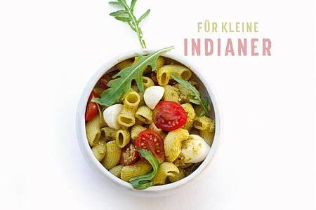Für den Pesto-Nudel-Salat werden Nudeln gekocht, Tomaten halbiert, Mozzarella geschnitten und Rucola gewaschen. Am Ende wird alles vermengt und mit grünem Pesto serviert. Foto: Daniela Sonntag/Trias Verlag/dpa-tmn