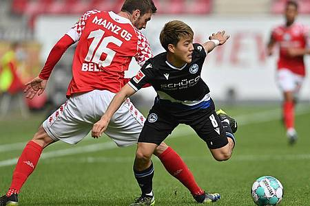 Mainz` Abwehrspieler Stefan Bell (l) versucht Bielefelds Stürmer Ritsu Doan vom Ball zu trennen. Foto: Torsten Silz/dpa