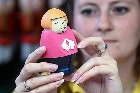 Sina Klement komplettiert in der Schauwerkstatt der Seiffener Volkskunst in Seiffen eine Merkel-Figur. Foto: Hendrik Schmidt/dpa-Zentralbild/ZB