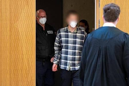 Der Angeklagte (im karierten Hemd) wird in den Sitzungssaal geführt. Foto: Sven Hoppe/dpa