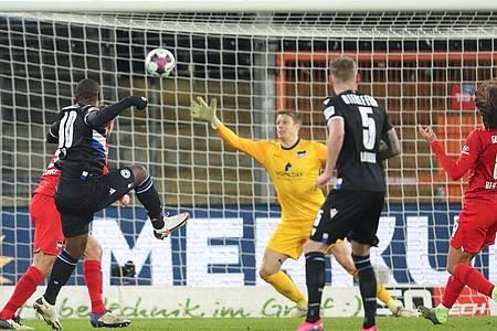 Bielefelds Reinhold Yabo (l) erzielt den Treffer zum 1:0 gegen Herthas Torwart Alexander Schwolow (M). Foto: Friso Gentsch/dpa