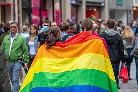 Zwei Frauen laufen umhüllt von einer Pride-Flagge durch die Münchner Innenstadt. Foto: Lino Mirgeler/dpa