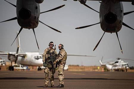 Deutsche Soldaten stehen am Flughafen in Gao und sichern ein Transportflugzeug. Foto: Arne Immanuel Bänsch/dpa