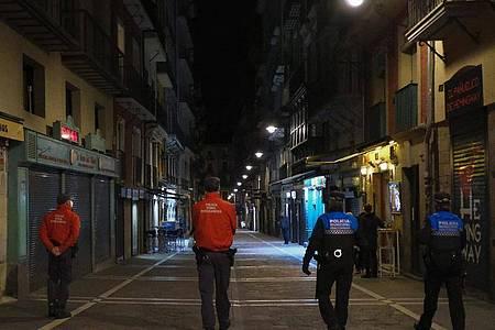 Polizisten patrouillieren auf einer Straße, bevor alle Bars und Restaurants um 22 Uhr geschlossen werden. Wegen der sprunghaft steigenden Corona-Infektionszahlen in Europa gelten seit Samstag um Mitternacht Reisewarnungen für weitere Regionen in 15 EU-Ländern. Foto: Alvaro Barrientos/AP/dpa