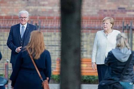 Bundespräsident Frank-Walter Steinmeier und Bundeskanzlerin Angela Merkel posieren für ein Foto vor der Kirche St. Peter und Paul in Potsdam. Foto: Christoph Soeder/dpa