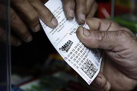 Ein Lottospieler kauft Mega Millions Lotterielose an einem Kiosk. (Archivbild). Foto: Matt Rourke/AP/dpa