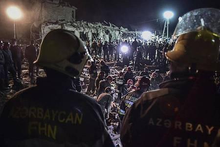 Soldaten und Feuerwehrleute vor zerstörten Häusern in Ganja, Aserbaidschans zweitgrößter Stadt. Foto: Ismail Coskun/IHA/AP/dpa