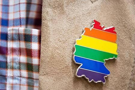 Anstecker mit dem Umriss von Deutschland in Regenbogenfarben. Foto: Sebastian Gollnow/dpa