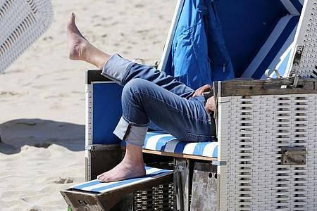 Entspannung im Strandkorb an einem Strand in Schleswig-Holstein. Foto: Bodo Marks/dpa