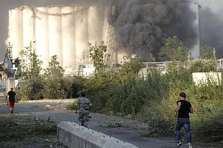Sicherheitsleute laufen zum Ort der Explosion im Hafen von Beirut, während über dem Gebäude Rauch aufsteigt. Foto: Hussein Malla/AP/dpa