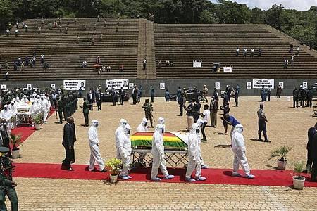 Menschen in Schutzkleidung tragen den Sarg der an Corona verstorbenen Ministerin Dr. Ellen Gwaradzimba. Seit Beginn der Pandemie sind inSimbabwe insgesamt vier Minister an Covid-19-Komplikationen gestorben. Foto: Tsvangirayi Mukwazhi/AP/dpa