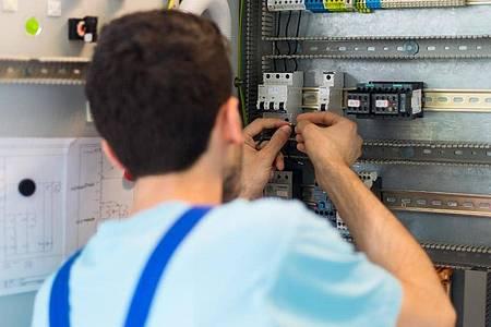 Der 19-jährige Mohammad aus Afghanistan arbeitet in einem Leipziger Ausbildungszentrum von Siemens an der Verdrahtung eines Schaltschranks. Foto: Monika Skolimowska/dpa-Zentralbild/dpa