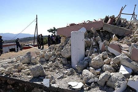 Feuerwehrleute stehen neben der zerstörten griechisch-orthodoxen Kirche Profitis Ilias, nachdem das Dorf Arkalochori im Süden der Insel Kreta von einem Erdbeben erschüttert wurde. Foto: Harry Nakos/AP/dpa