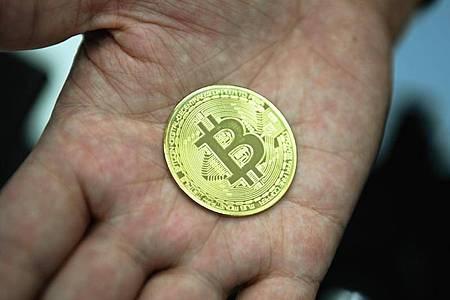 Ein Mann hält eine nachgemachte Münze mit dem Bitcoin-Logo in den Händen. Foto: Nicolas Armer/dpa