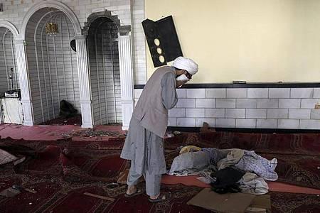 Ein Student weint in der Moschee nach der Bombenexplosion. Bei einem Anschlag in Kabul sind nach Angaben der Polizei mindestens zwölf Menschen getötet worden. Foto: Rahmat Gul/AP/dpa