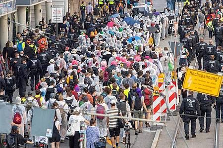 Ein Demonstrationszug läuft in Polizeibegleitung durch München. Foto: Peter Kneffel/dpa