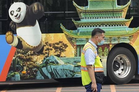 Ein Verkehrspolizist steht bei Probefahrten neben einem Bus, auf dem für den Vergnügungspark von Universal Studios geworben wird. Foto: Ng Han Guan/AP/dpa