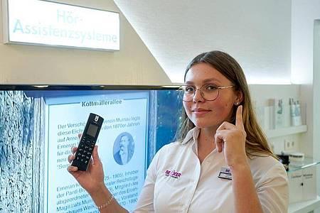 Die angehende Hörakustikerin Carolin Haag erklärt in einer Filiale ihres Ausbildungsbetriebs Becker Hörakustik ein Telefon. Es kann mit dem Hörassistenzsystem kommunizieren. Foto: Thomas Frey/dpa-tmn
